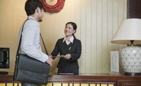 ホテルフロントで中国語通訳をする女性